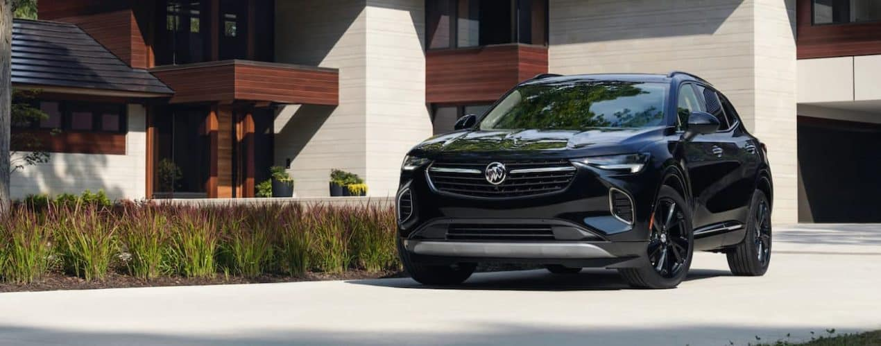 A black 2021 Buick Envision is parked outside of a modern home.