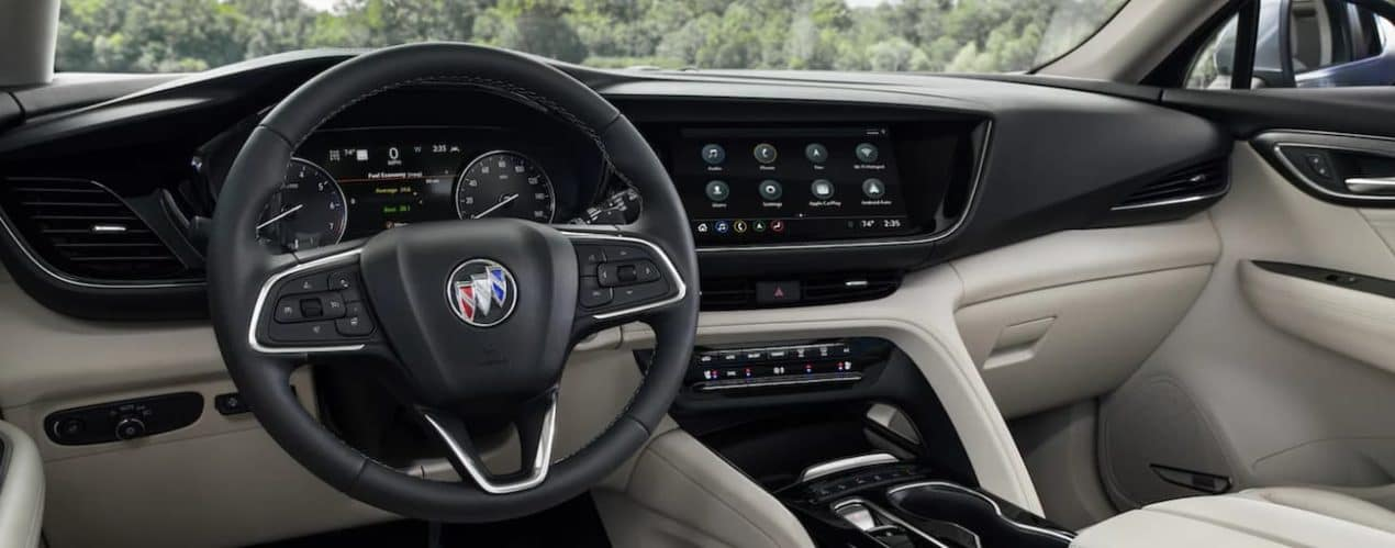 The interior of a 2021 Buick Envision shows the steering wheel and infotainment screen.