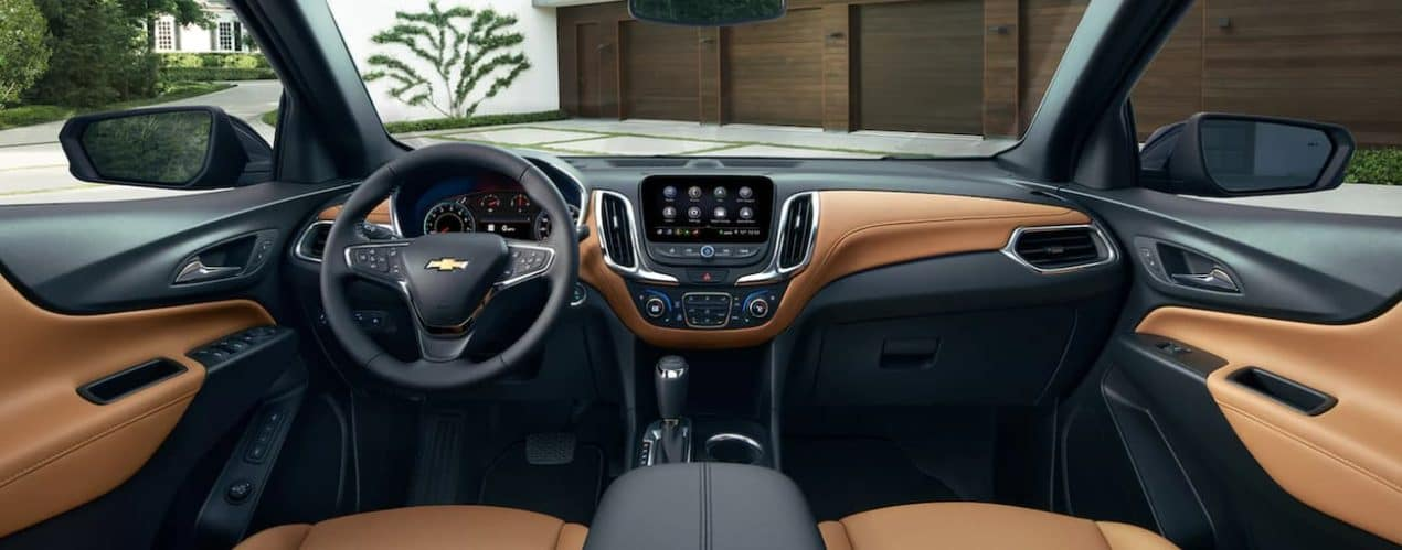 The tan and black interior of a 2021 Chevy Equinox shows the steering wheel and infotainment screen.