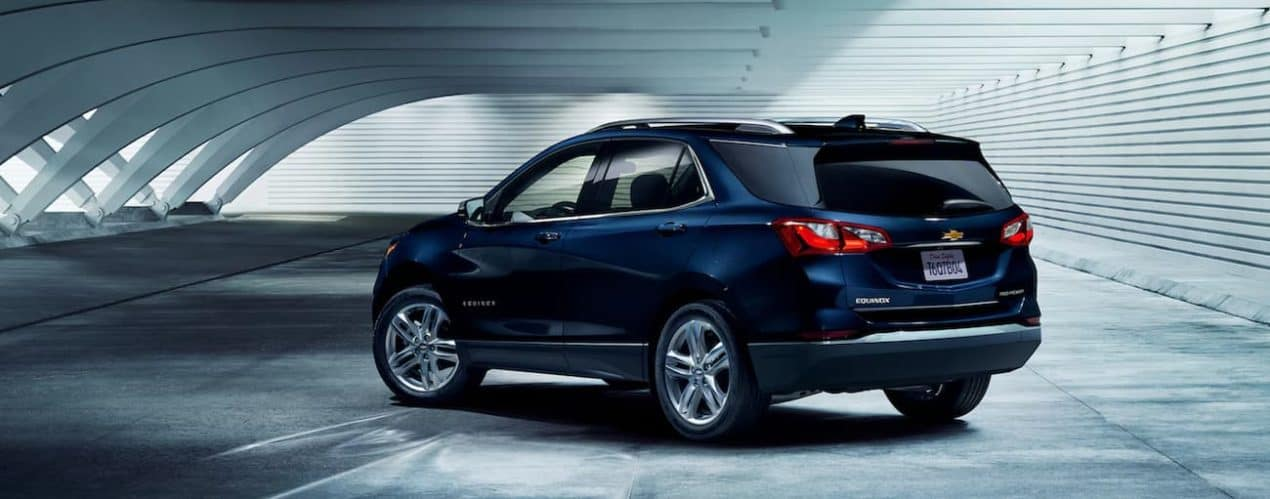 A blue 2021 Chevy Equinox is shown from the side parked in a modern parking garage.