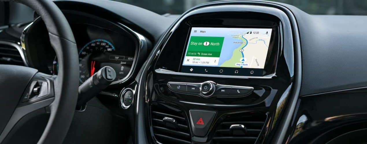 The black interior in a 2021 Chevy Spark shows the steering wheel and infotainment screen.