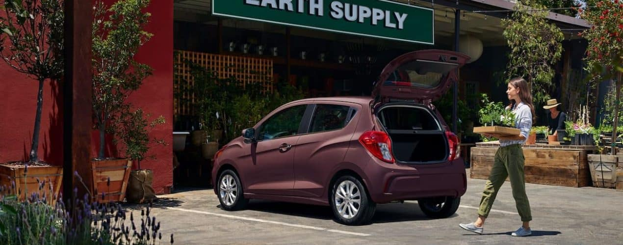 A pink 2021 Chevy Spark is shown from the back with the lift gate open.