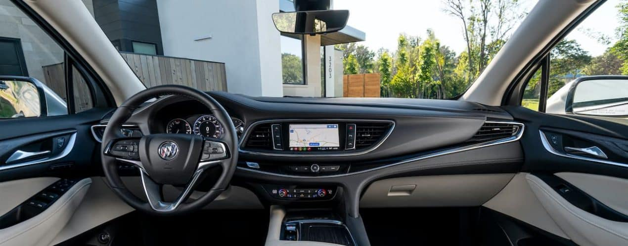 The interior of a 2022 Buick Enclave shows the steering wheel and infotainment screen.