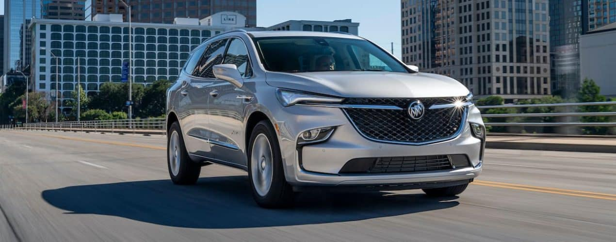 A silver 2022 Buick Enclave is driving through a city.