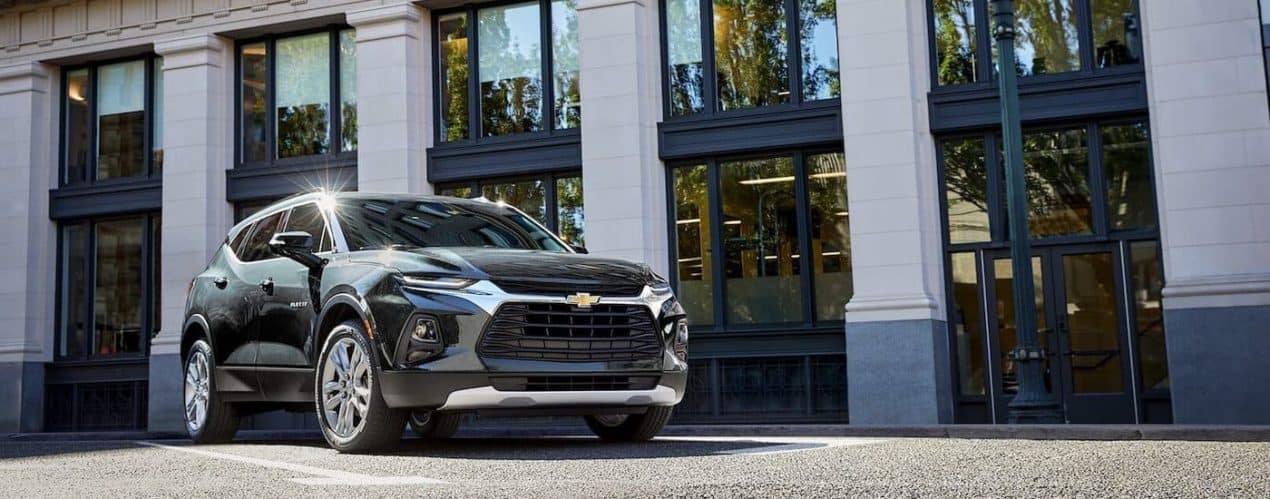 A black 2022 Chevy Blazer RS is shown parked in front of a building on a sunny day.