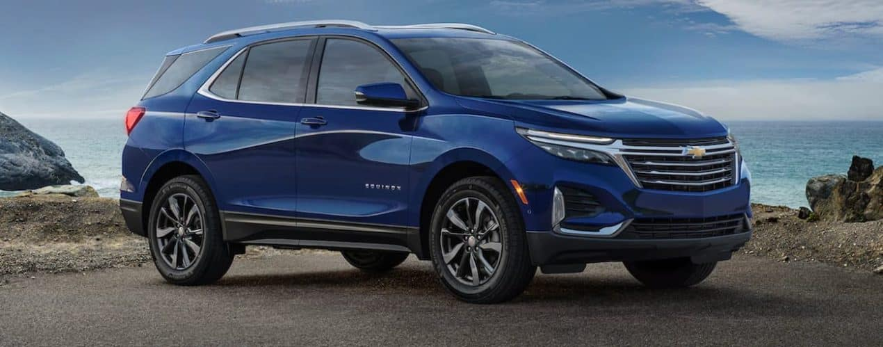 A blue 2022 Chevy Equinox is parked under an open sky.