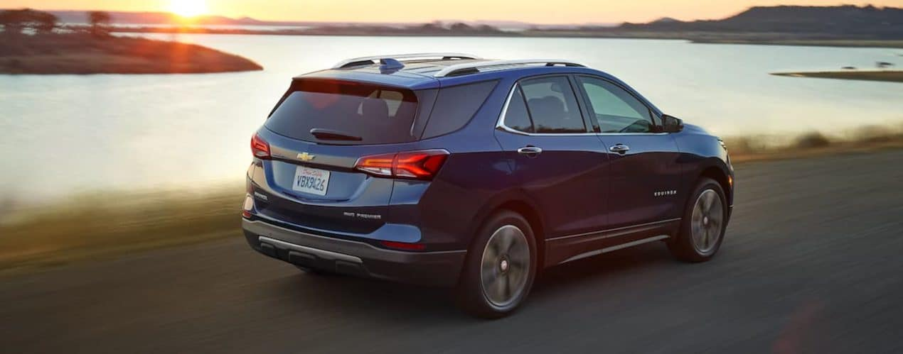 A blue 2022 Chevy Equinox is driving past a lake.
