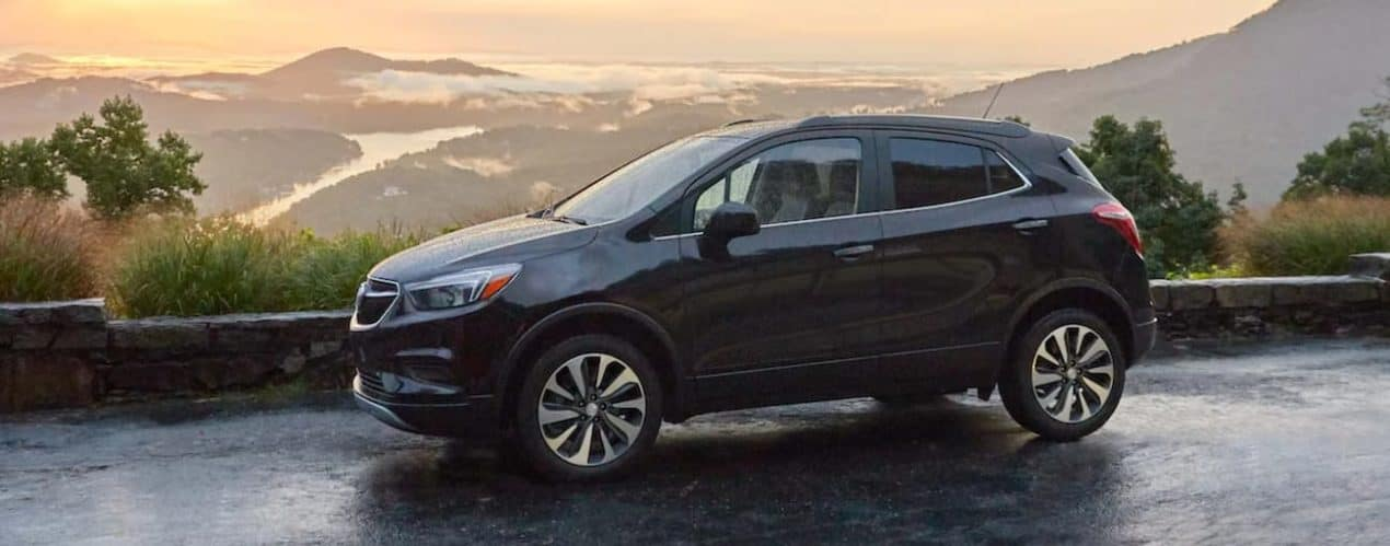 A black 2022 Buick Encore is shown from the side parked in front of a mountain range.