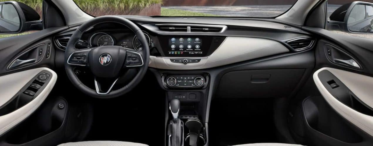 The black interior of a 2022 Buick Encore GX shows the steering wheel and infotainment screen.