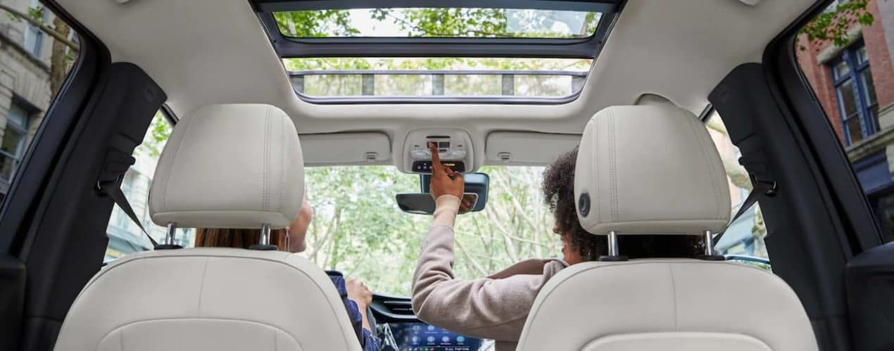 Two people are shown sitting in a 2022 Buick Encore GX.