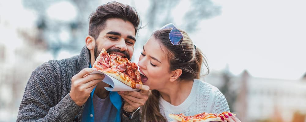 Couple eating pizza outdoors and smiling.They are sharing pizza in a outdoor cafe.