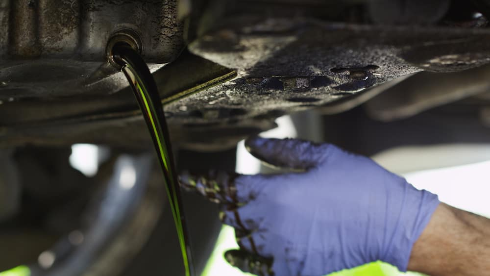 Blue glove mechanic draining dirty oil from under car