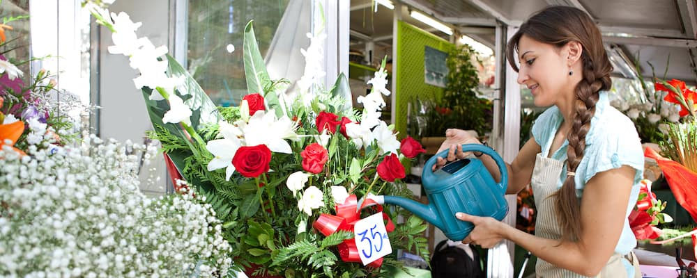 Side view of an attractive florist shop attendant watering and tendering her floral pots and arrangements in her flowers florist store during a sunny day, outdoors.