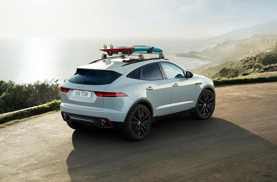 2019 Jaguar E-PACE Driving Along Ocean with Surfboard Attached to Roof Rails