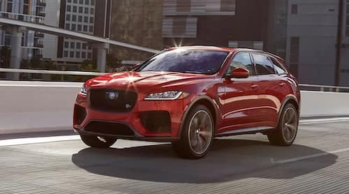 New red Jaguar driving on road