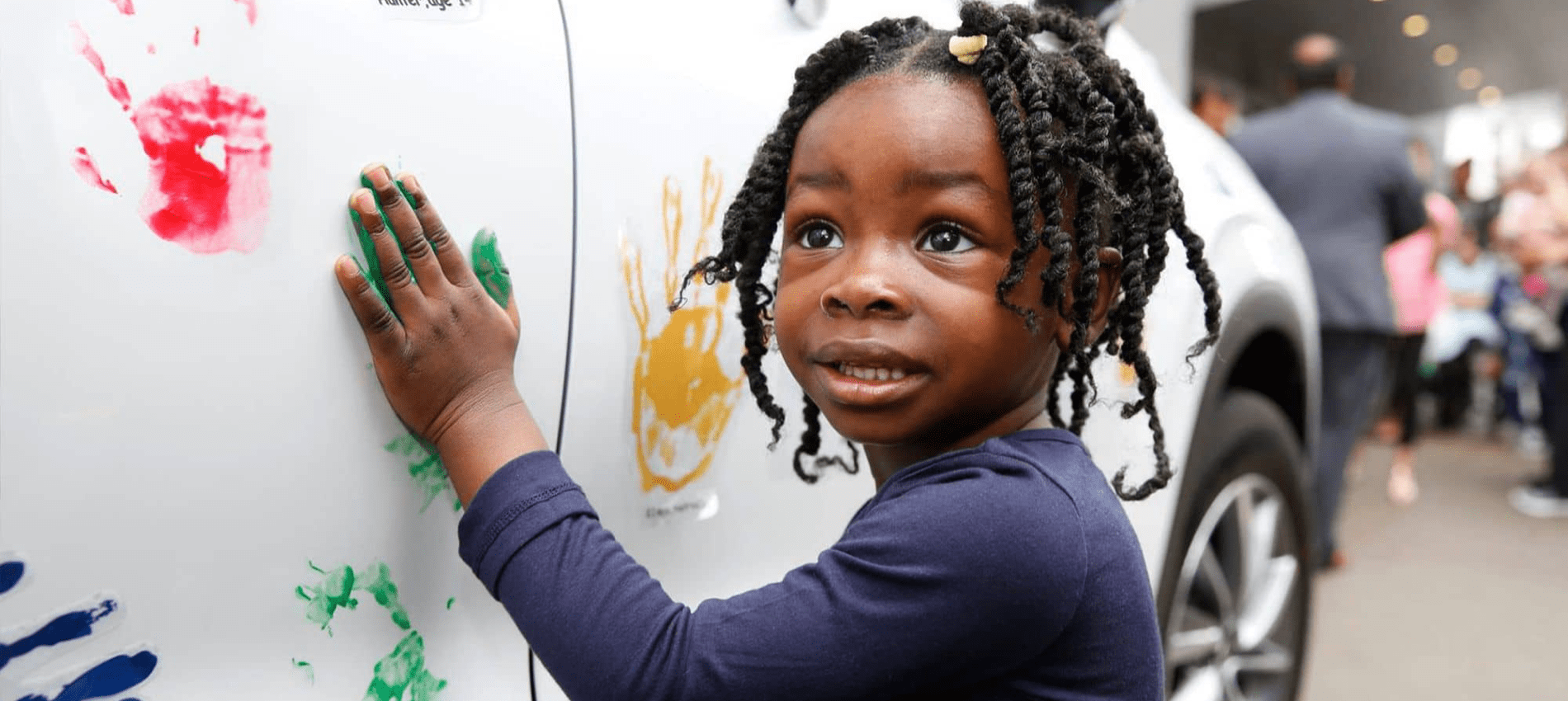 girl paints handprints on car for Hyundai Hope On Wheels