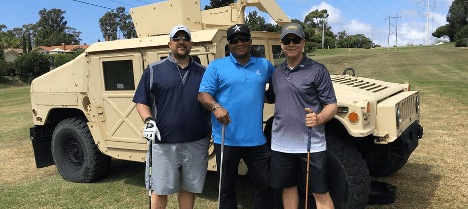 golfers stand in front of military vehicle