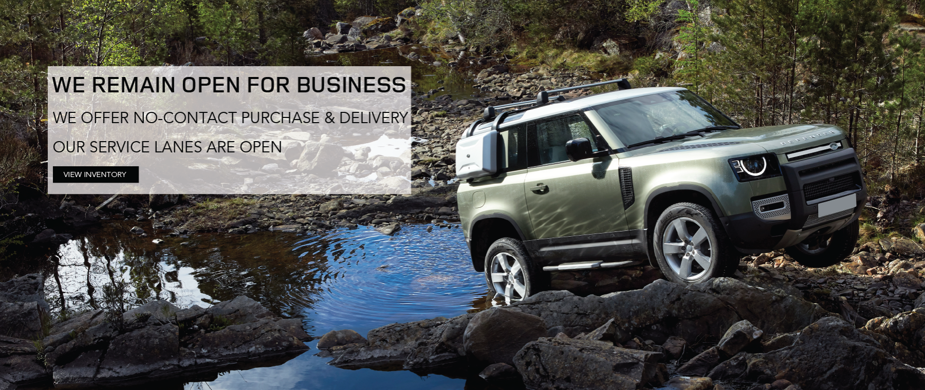 Green 2020 Land Rover Defender on rocks in middle of river. We're Open for Business. Click to view inventory.
