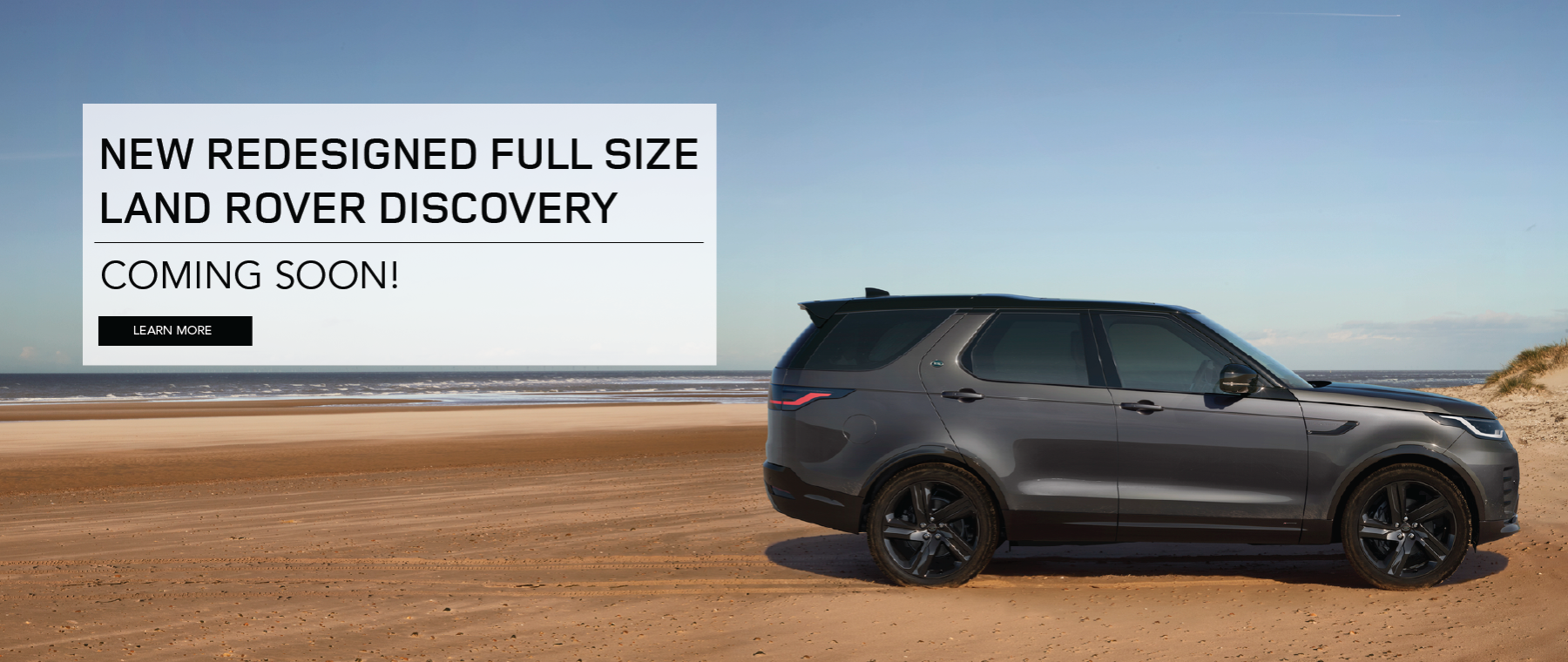 Black 2021 Land Rover Discovery on on beach near water. Click to learn more.
