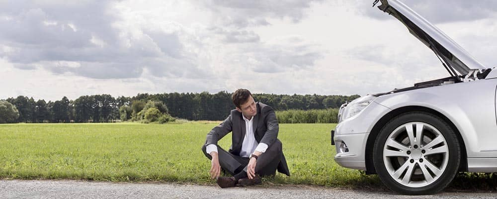 Guy sitting on side of road next to broken down car
