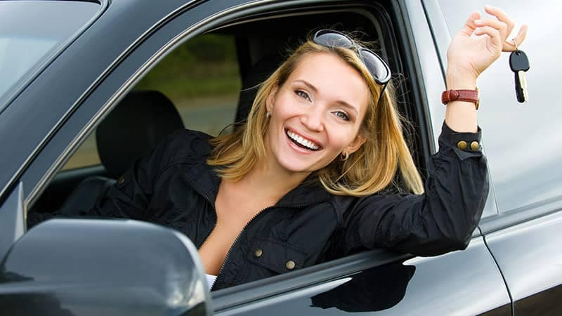 Blonde woman in front seat holding car keys