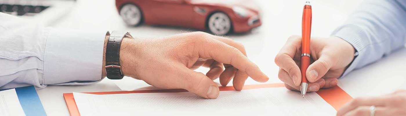 woman signing document at a car dealership