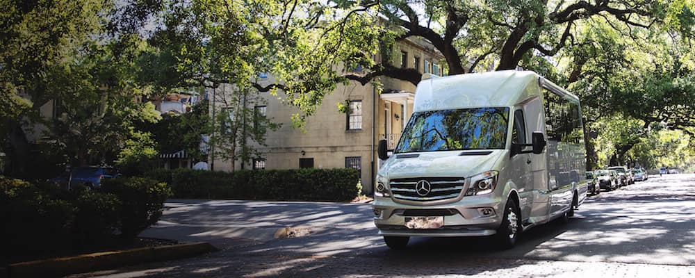 Atlas Touring Coach driving on a shaded street with many trees