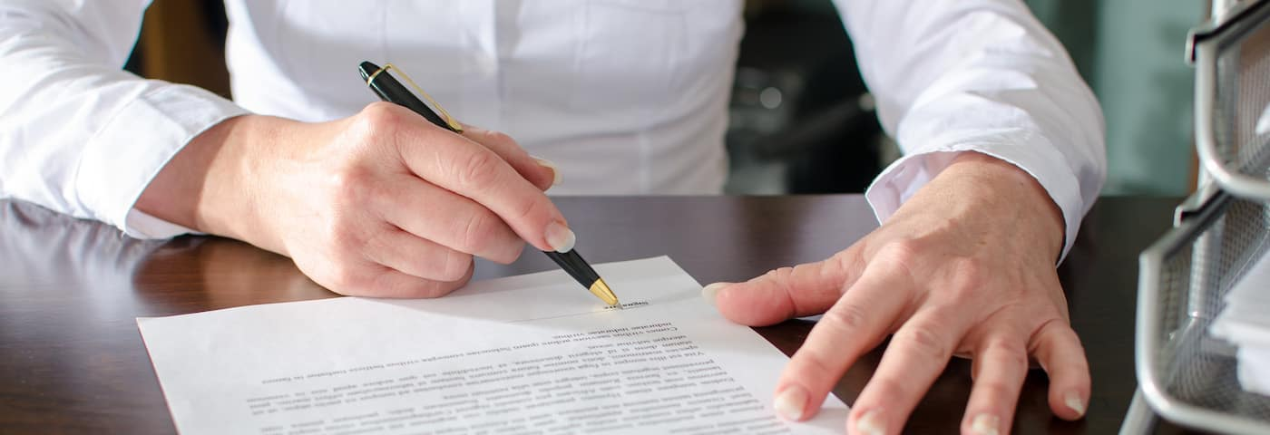 woman signing car dealership contract