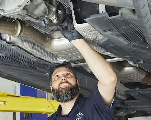 Mercedes-Benz Tech Working Underneath Car