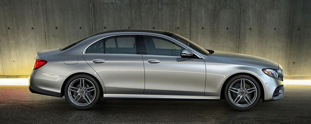 Silver E-Class sedan parked in front of gray concrete background