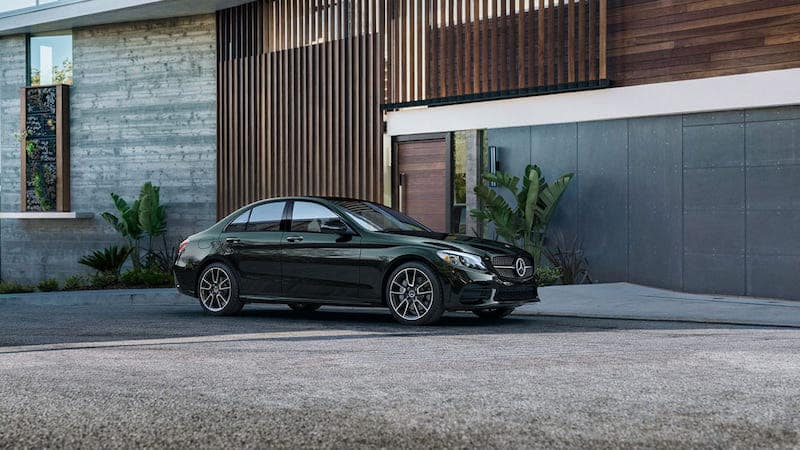 Black C-Class sedan parked in front of a garage