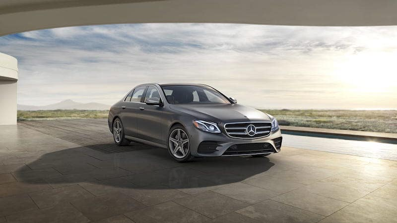 Gray E-Class parked in front of a sky at dusk