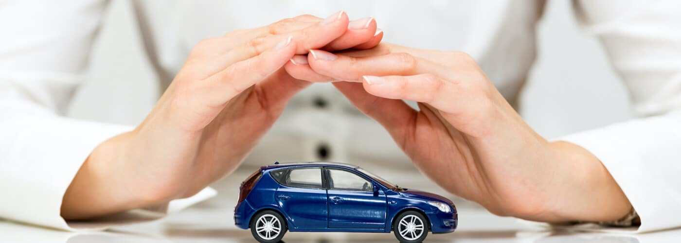 Person protects small blue car with their hands