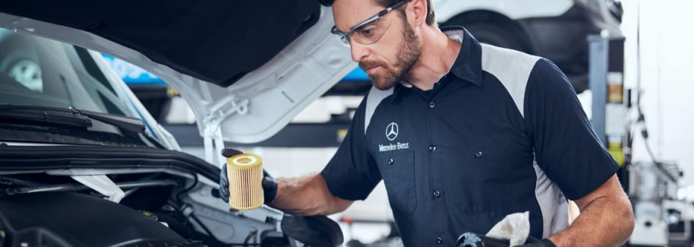 Mercedes-Benz technician servicing vehicle with Mercedes-Benz oil change service