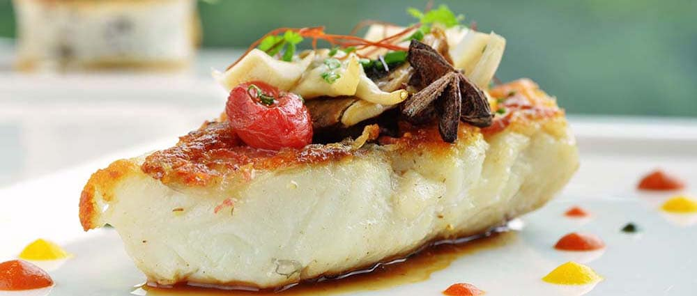 Close up of grilled fish topped with vegetables