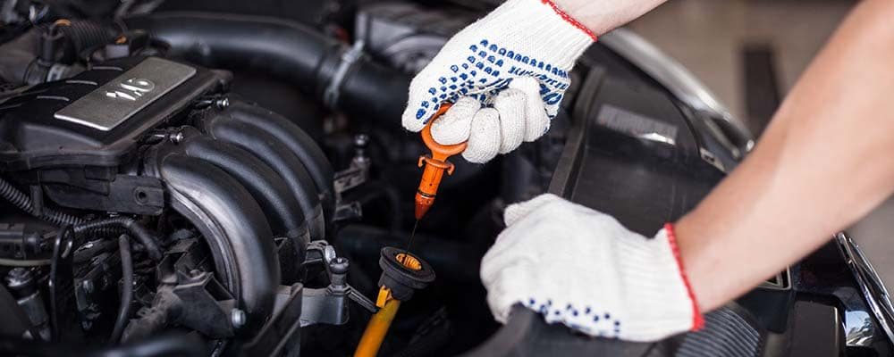 Close up of gloved hands performing an oil change