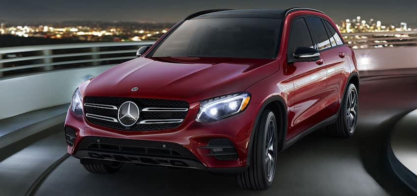 Red GLC driving down a highway at night