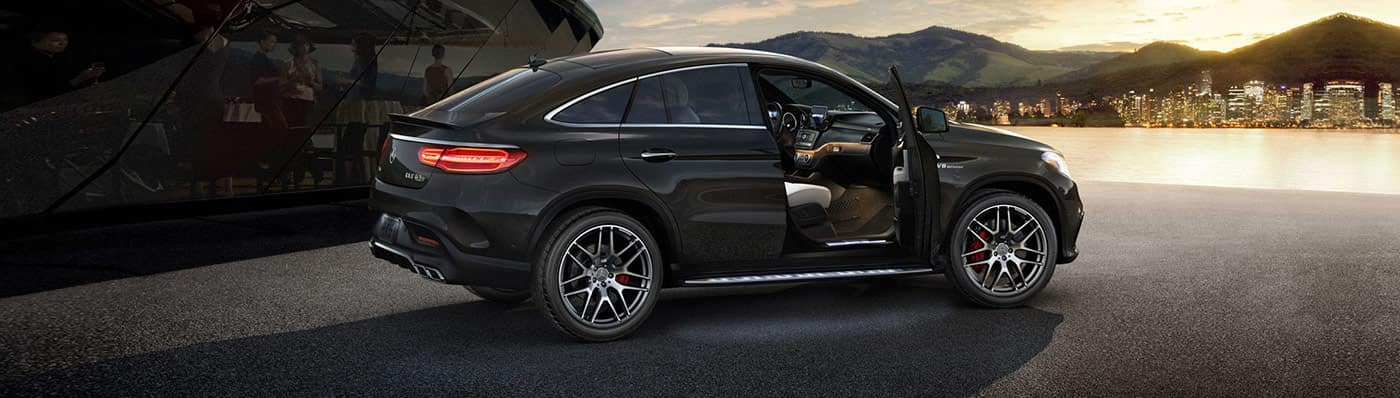 Mercedes-Benz car with an open door parked in front of a city