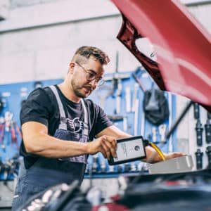 Image shows a MINI service advisor adding oil to a MINI vehicle in a garage.