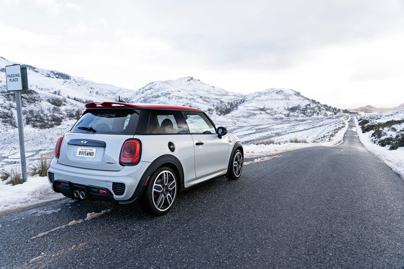 MINI parked on road with snow-covered mountains in the background.