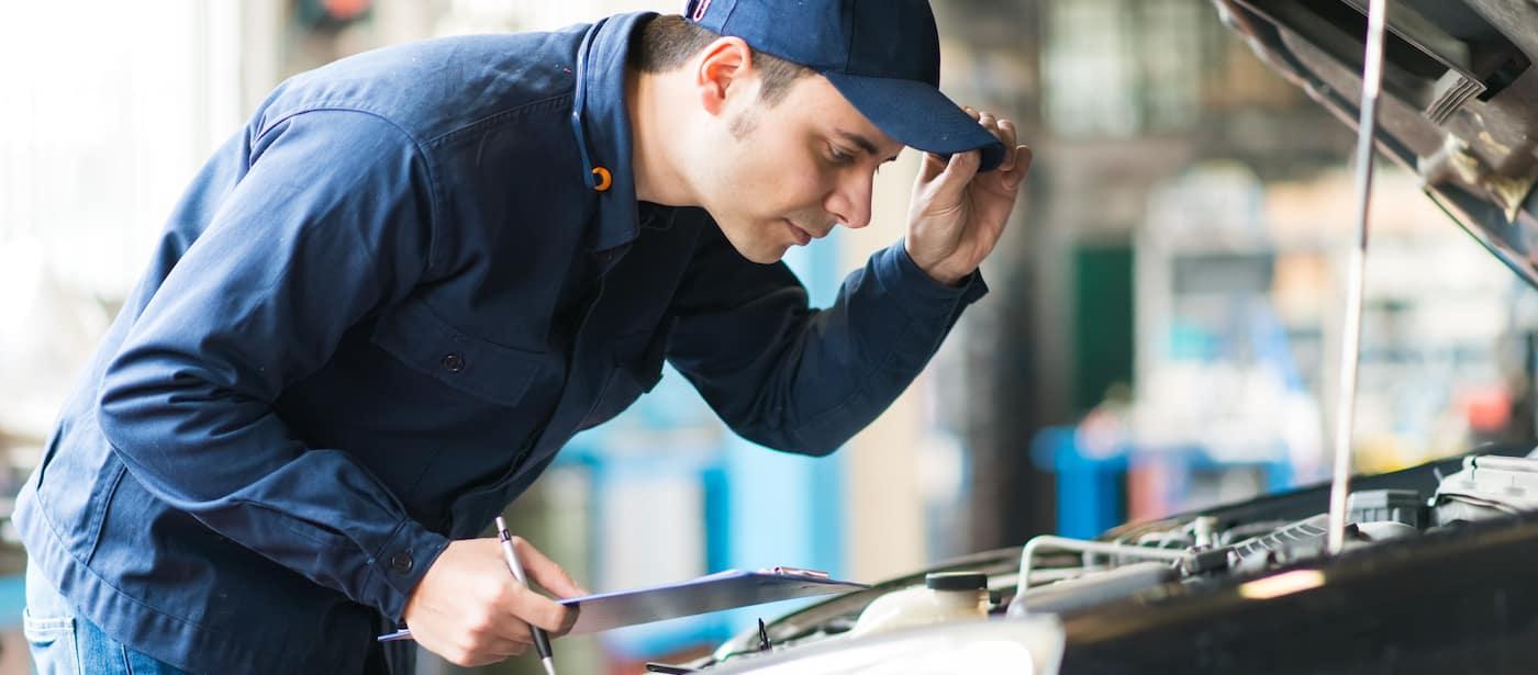 Mechanic with hat examining engine