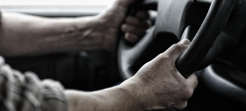 Worker with hands holding steering wheel.