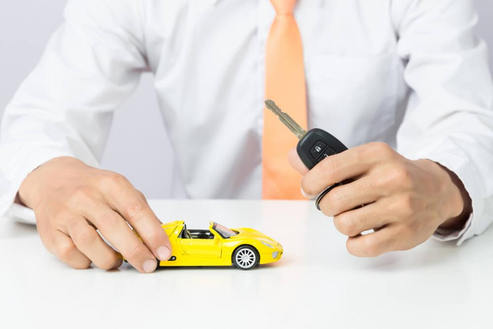 Finance logo - man holding keys and a yellow toy sports car