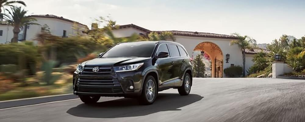 2018 Toyota Highlander driving past homes