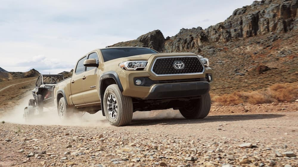 2019 Toyota Tacoma V6 towing a trailer across desert landscape