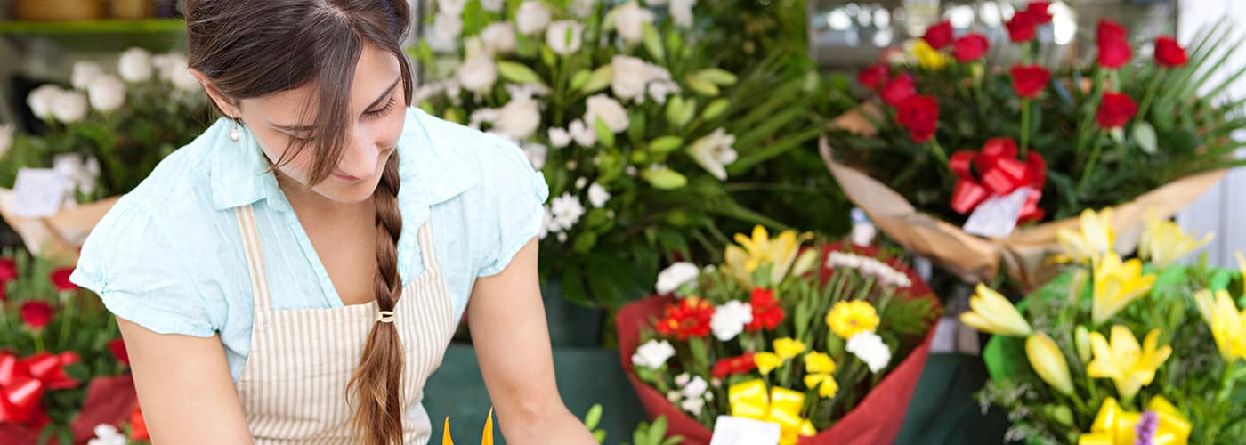 businesswoman florist arranging and tendering her flowers