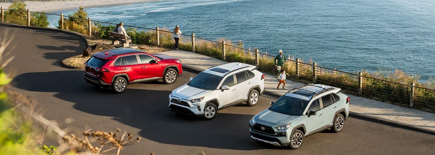 three Toyota Rav4 models on cliff overlooking the ocean