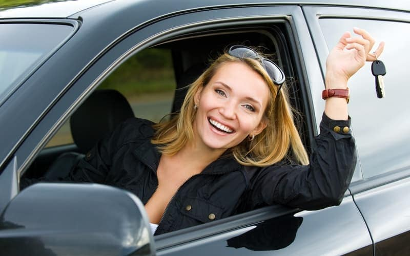 woman in front seat holding car keys