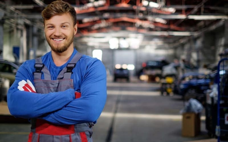 smiling mechanic standing in service department