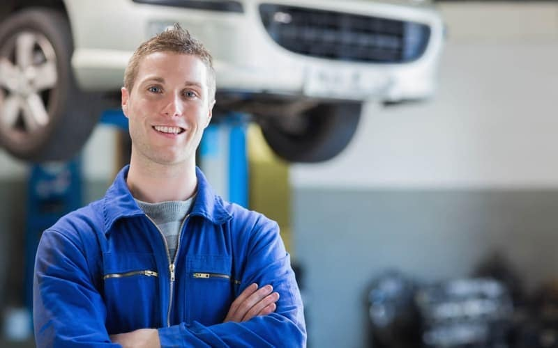 mechanic standing in front of car in service department